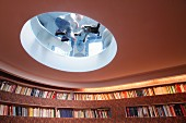 Library with curved walls, fitted shelving and transparent glass panel in circular ceiling cut-out with view of child and dog