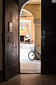 View through open, rustic, wooden front door of bicycle parked under arcades and shop with painted shutters
