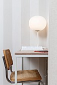 White, spherical table lamp on delicate table and cantilever, cane chair