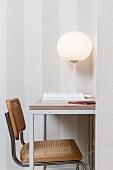 weiße Kugel-Tischleuchte auf filigranem Tisch mit frei schwingendem Korbgeflechtstuhl
