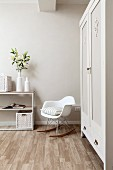 White, designer rocking chair next to painted wardrobe and vase of lilies on top of open-fronted shelving in corner of bedroom