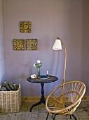 Stuhl aus Geflecht neben Stehleuchte und Bistrotisch vor mauvefarbener Wand mit aufgehängten Vintage Fliesen