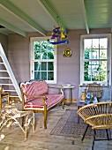 Gepolsterte Sitzbank mit rot-weiss gestreiftem Bezug, Stuhl aus Geflecht in ländlichem Wohnzimmer