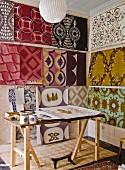 Desk in studio with wallpaper designs on walls