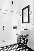 Sink on wrought iron sewing machine frame in white, modern bathroom with shower