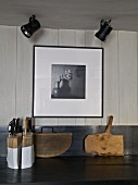 Knife block and rustic chopping boards on kitchen worksurface below ceiling spotlights and black and white photo on white wooden wall