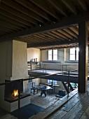 Blick von Galerie auf Kaminfeuer in reduziertem restauriertem Wohnraum mit Holzdecke und rustikalem Flair