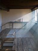 Lichteinfall durch Fenster auf restaurierte Galerie, rustikaler Dielenboden mit antikem Wandtisch