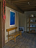 Simple, retro bench on rustic wooden floor in restored interior with wood-beamed ceiling and modern, blue artwork on wall