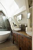Custom, wood-veneer washstand with twin, countertop basins next to free-standing bathtub