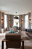 Elegant lounge area with brown leather sofa and chairs, semicircular window bay with sconce lamps between windows and floor-length curtains
