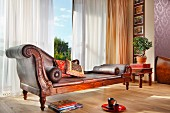 Elegant, antique chaise longue in front of panoramic window with airy curtains in traditional interior