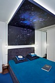 Double bed with blue bed linen below starry-sky canopy made from back-lit, printed glass on ceiling and wall in modern bedroom