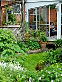 View from flowering garden to extension with glass sliding door