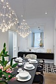 White place settings on black table below designer, LED pendant lamps in dining room