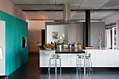 Kitchen island with adjoining table top and bar stools; fitted electrical appliances in turquoise custom cupboards