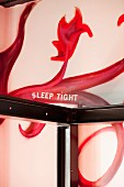 Steel profile four poster bed frame and imaginative mural on wall with motto 'Sleep tight'