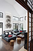View through open Shoji sliding doors of charcoal sofa combination, black and white graphic artwork and windows with view of garden