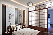 Japanese-style bedroom with sliding shoji walls and drawings of bamboo in niche behind double bed