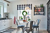Cosy, Scandinavian kitchen with black and white colour scheme, central table with vintage chairs and textiles in checks and stripes