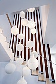 White spherical pendant lamps hanging at different heights in open-plan stairwell