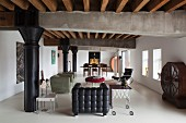 Loft-apartment lounge with black leather armchair, side table and round vintage cabinet against wall