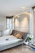 Doppelbett in Designerstil mit gebogenem Kopfteil und grauem Bezug in modernem Schlafzimmer