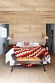 Überwurf mit Retro Zickzackmuster auf Doppelbett vor Wand mit Holzverkleidung, vorne Kleiderbank im Stil eines antiken Scherenstuhls