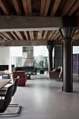 Loft apartment with black metal pillar under girder structure, dining area to one side and lounge area with retro armchairs and sofa