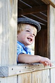 Little boy looking out of window of wooden cabin