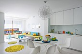 White, open-plan interior; dining area with classic shell chairs opposite white fitted kitchen with round, yellow rugs providing a splash of colour