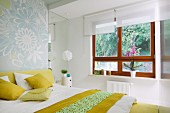 Bedroom with double bed, white and yellow bed linen and scatter cushions and wooden windows with white roller blinds and view of garden