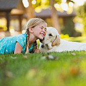 Girl and young dog lying on lawn