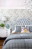Double bed with grey upholstered headboard against patterned wallpaper in elegant bedroom