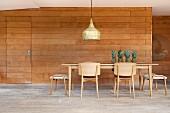 Stühle, Hocker und Tisch aus hellem Holz, darauf frische Ananas, oberhalb Vintage Pendelleuchte, holzverkleidete Wand