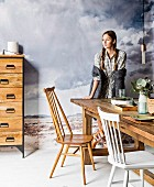 Young woman next to rustic wooden table, wooden chair, white-painted chair and chest of drawers in front of mural of grey cloudy sky