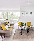 Loungebereich mit Sofa und Klassikerstuhl gelb lackiert um Couchtisch in offenem Wohnraum, im Hintergrund Essplatz vor Fensterfront