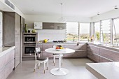 Tulip Table and upholstered Thonet chairs in classic dining area in modern fitted kitchen with U-shaped counters