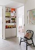 Grey-painted chair against wall and shelves and cupboards built into niche in foyer