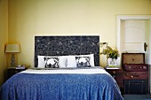 Vintage suitcases stacked against country-house interior door and bed with floral headboard in bedroom