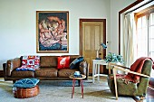 Cushion on pouffe in front of traditional brown leather sofa and fifties-style armchair in eclectic living room