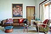 Sitzpouf mit Kissen vor braunem traditionellem Ledersofa und Sessel im Fiftiesstil in eklektischem Wohnzimmer