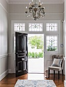 Elegant, Art-Nouveau foyer with open black front door and stained glass elements