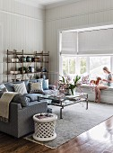 Sofa, coffee table, pale rug, woman seated on bay window seat and half-closed roller blinds