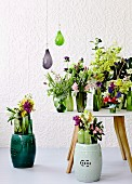 Spring bouquets in green glass vases on table and on ceramic stools against white structured wallpaper