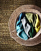 Colourful fabrics in seagrass basket on woven mat and silvery-green structured carpet