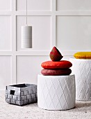 Brightly coloured cushions on stools with diamond structured surfaces and woven basket in front of white-panelled wall