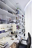 Modern office behind curtain - white shelves on wall with integrated desk and black office chair