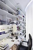 Moderner Arbeitsplatz hinter Vorhang - weisse Regale an Wand mit integrierter Schreibtischplatte, schwarzer Bürostuhl