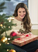 Cheerful young woman holding Christmas present